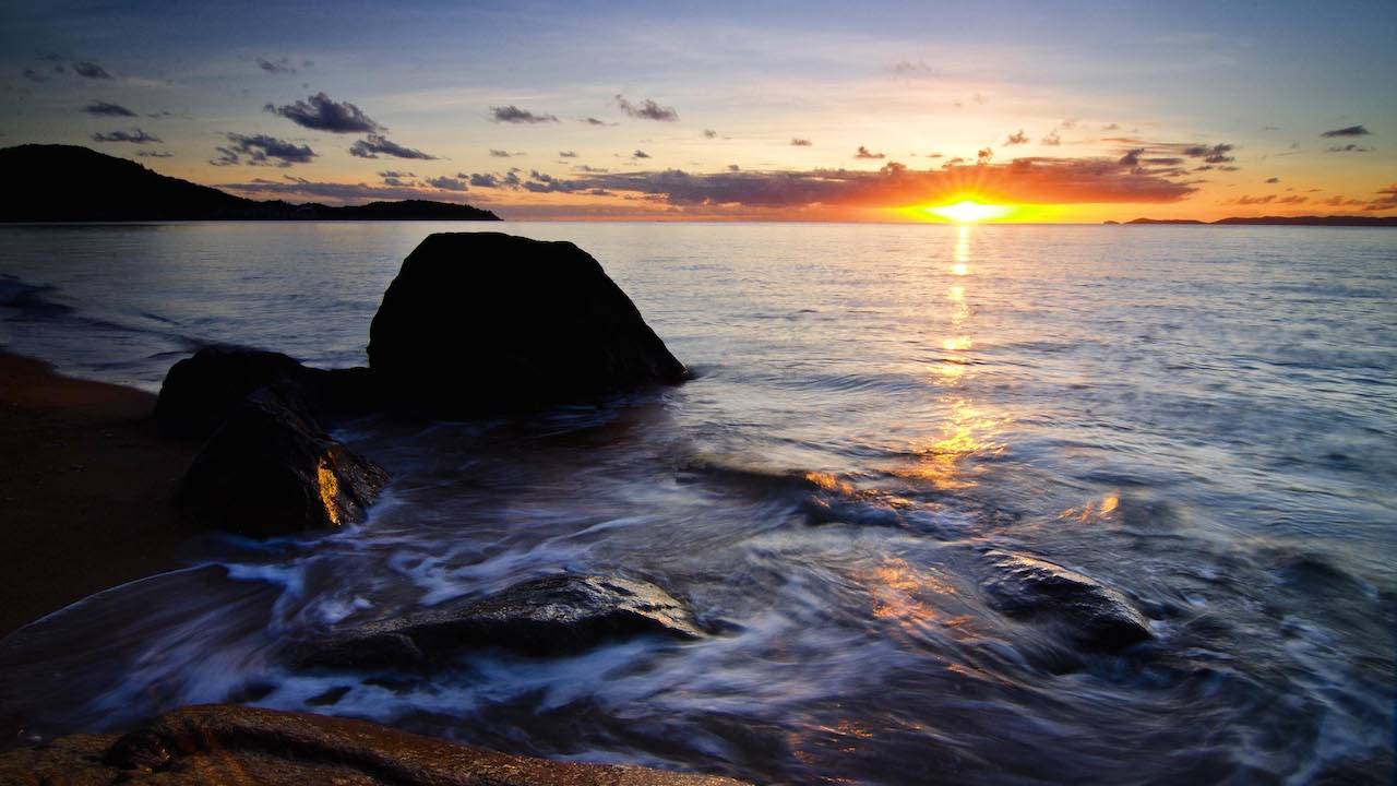 The sun sets behind the horizon as waves crash against a rock on the shore of Magnetic Island in Australia