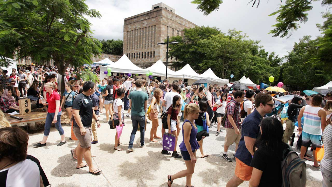 Many students walk around outside in UQ's campus enjoying Orientation Market Day
