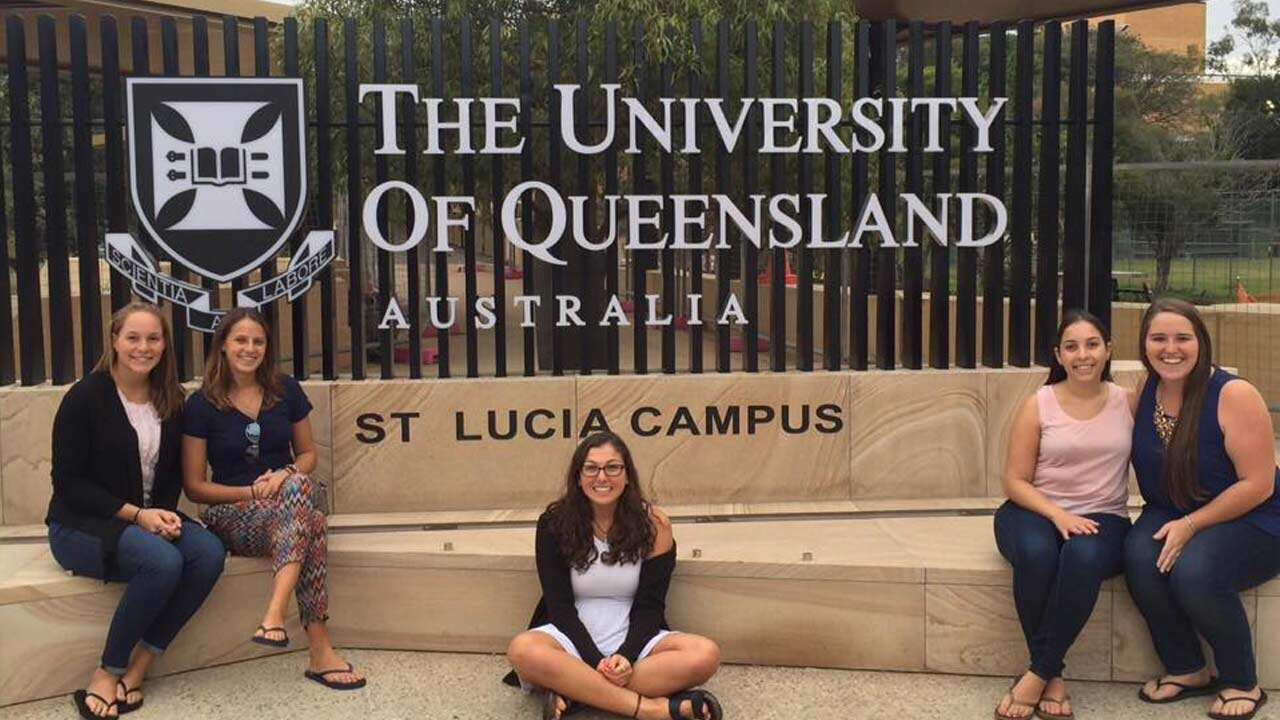 Five female students pose beside the 'University of Queensland, St. Lucia Campus' sign