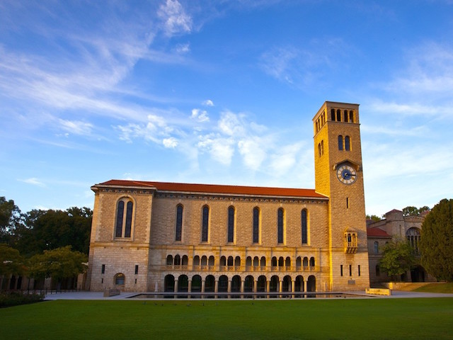 An ornate, brick building erect near a grassy quad below a blue sky on University of Western Australia's campus in Perth