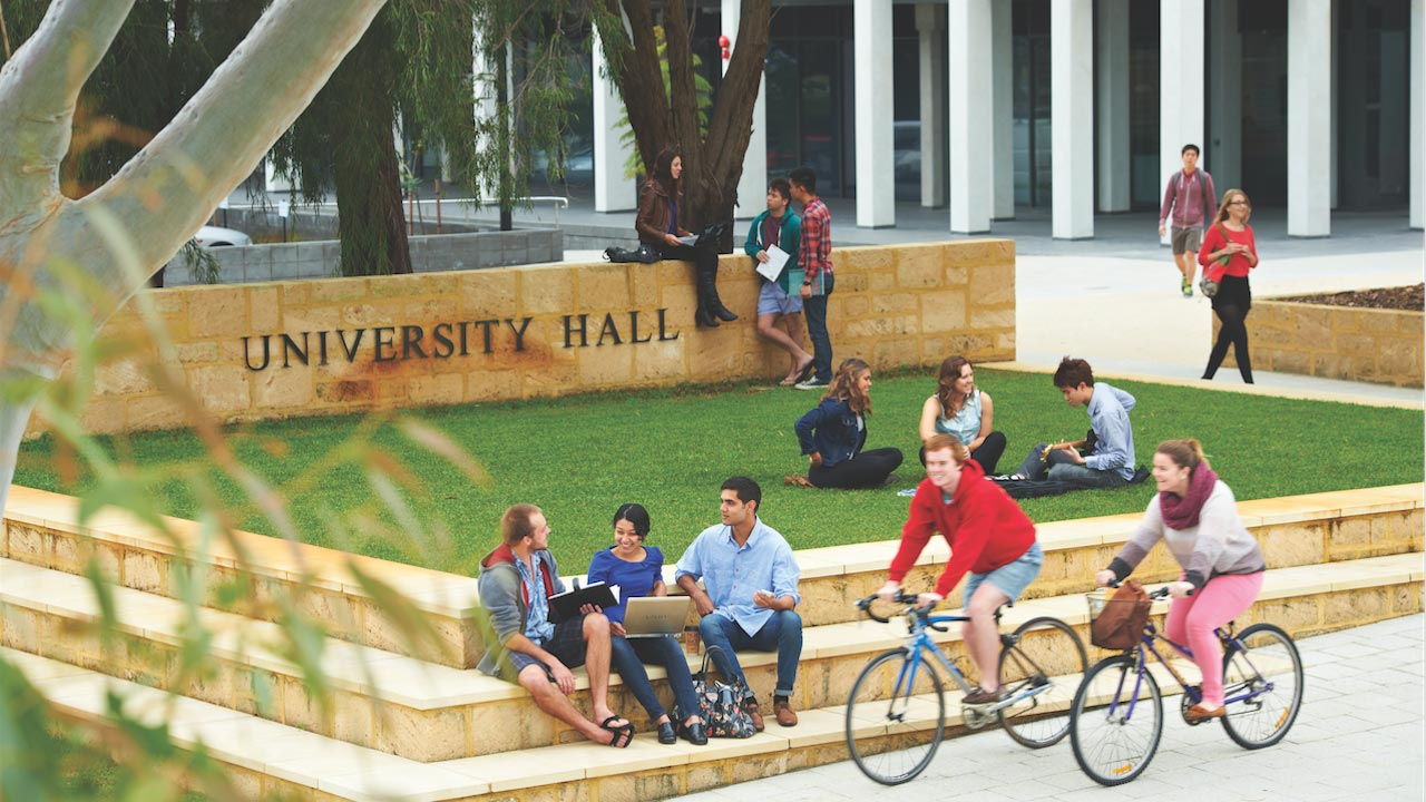 People gather on the grassy quad, two cyclists ride by on University of Western Australia's campus in Perth