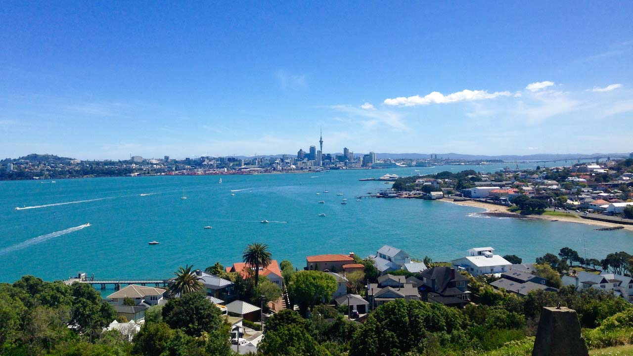Turquoise colored harbor with Auckland cityscape on the horizon