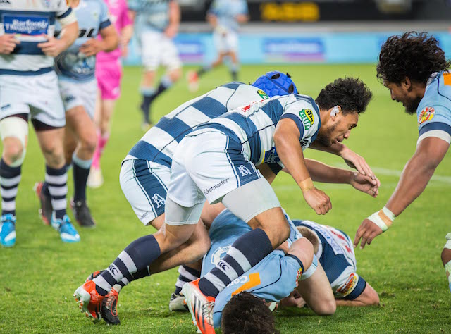 Two rugby players take a player from the opposing team down on the field during a game