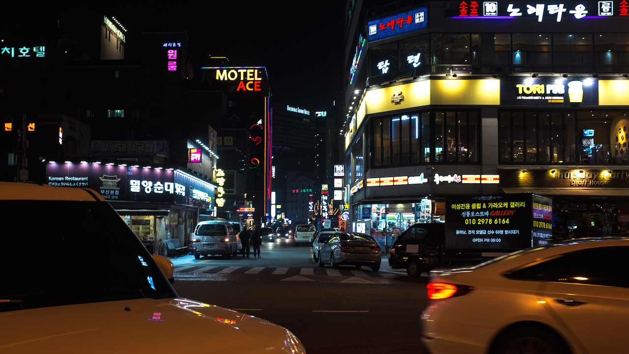 Illuminated buildings and taxis driving by at night in Korea