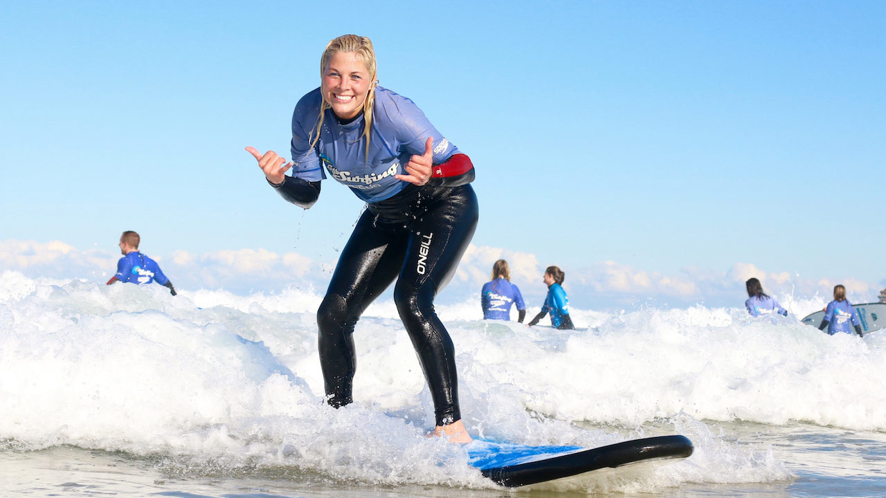 A woman smiles on her surfboard as a wave brings her to shore