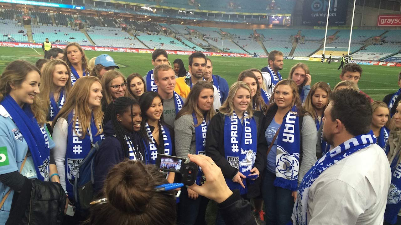 A group of students stand around a man explaining about Rugby on the stadium's field in Melbourne
