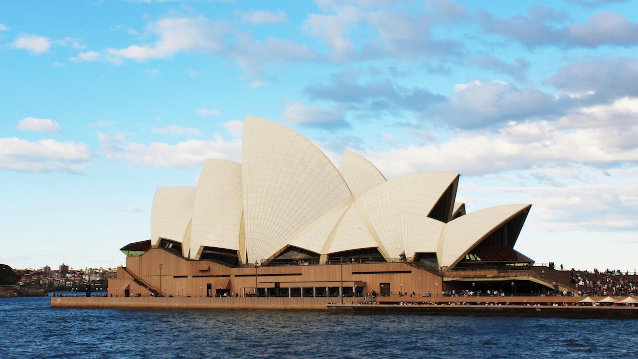 The Sydney Opera House sitting on the Harbour with a blue sky above