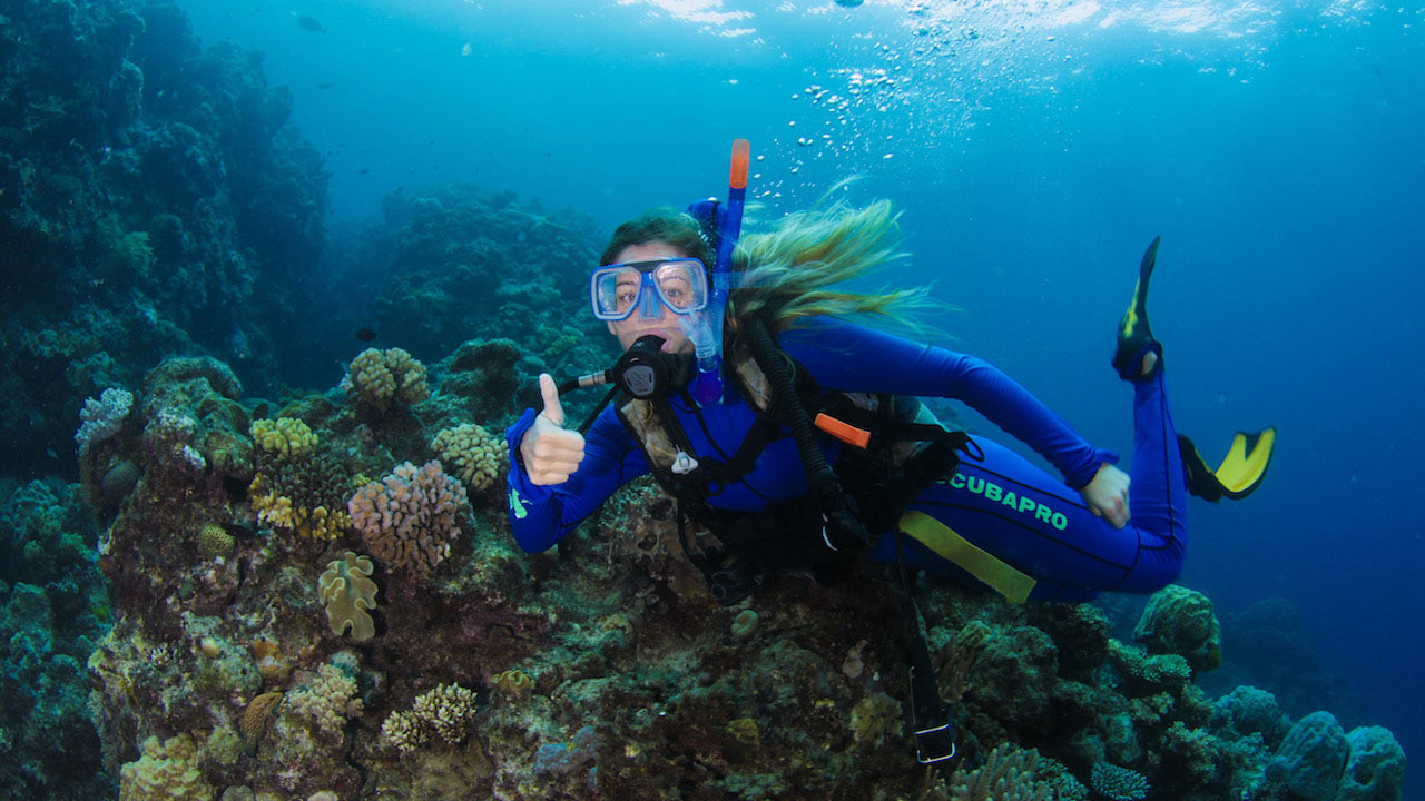 A female student scuba diving giving a thumbs up in the Great Barrier Reef