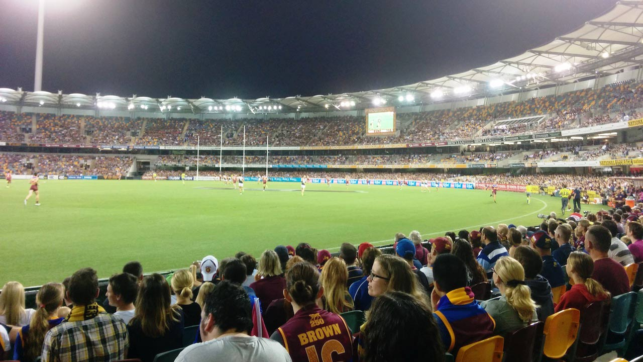 Fans sit in the stadium and watch the night time football match in Australia