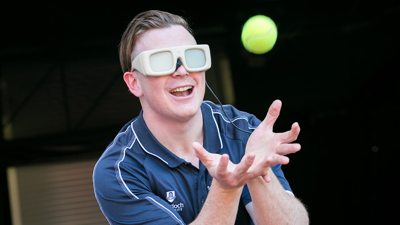 A student wearing special glasses has his hands open to catch a ball as part of sport science research at Murdoch University