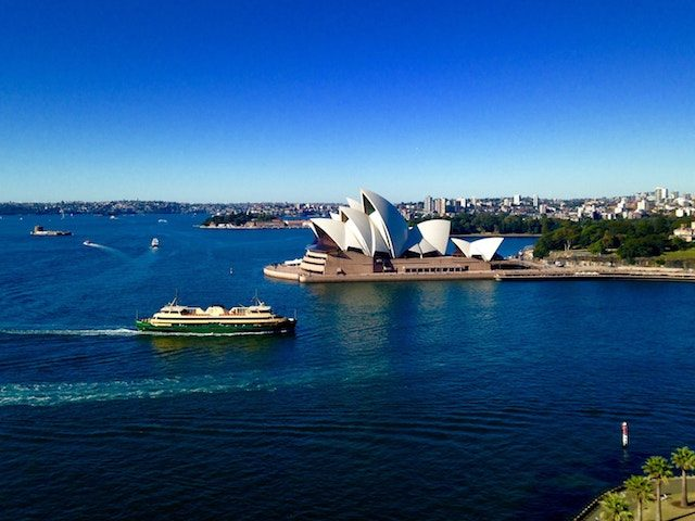 A boat cruises by the Sydney Opera House on a beautiful blue sky day