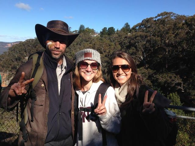 A man and two women pose together holding up peace signs amongst the Blue Mountains in Australia
