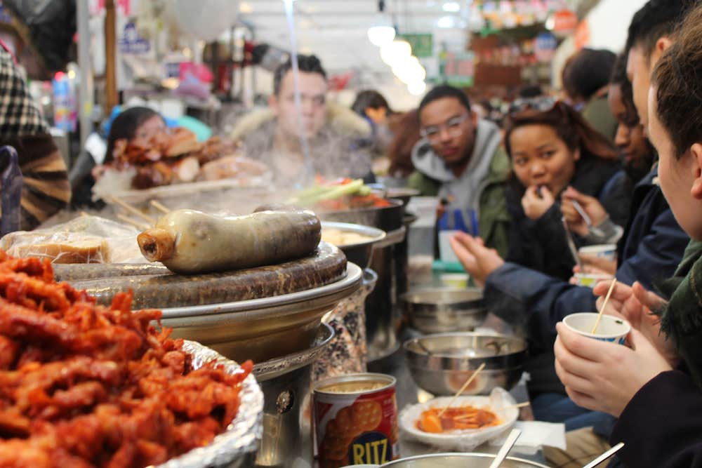 Group sitting around a counter having a meal at Gwangjang Market