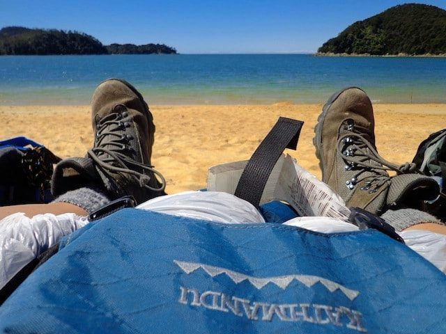 Hiking boots and backpack resting on a beach in New Zealand