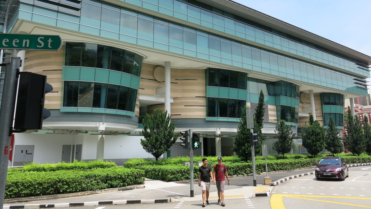 Two people walk on the sidewalk next to a building on Singapore Management University's campus
