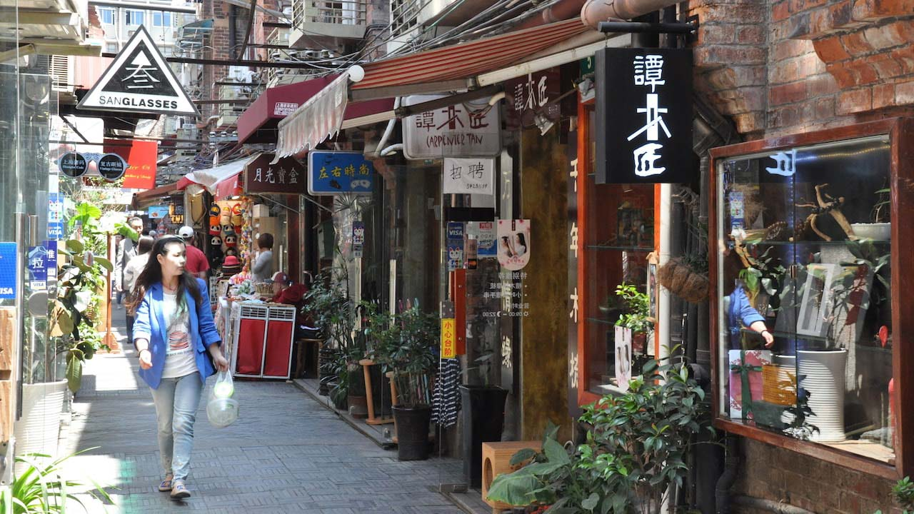 A woman walks down a laneway lined with stores and restaurants in Shanghai