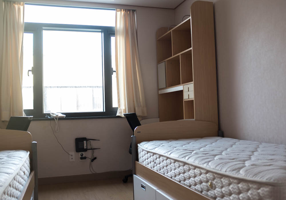 Room inside in a Korea University Dorm with a bed and desk