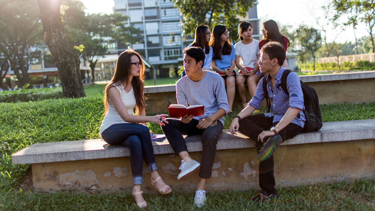 Students sitting together with an open book on campus at RMIT University Vietnam
