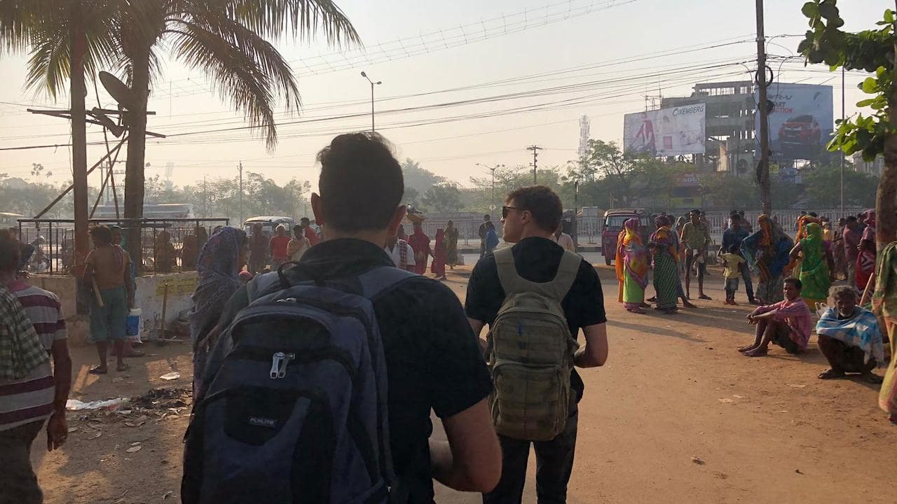 Two interns walking down street in India